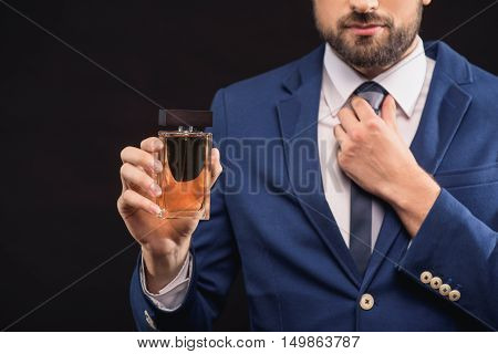 Confident businessman is holding cologne. She is standing and adjusting his tie. Isolated and copy space in left side
