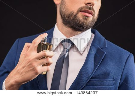 Sexy young man is perfuming himself with masculine cologne. She is standing and posing in suit with confidence. Isolated
