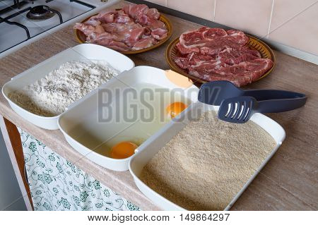 Ingredients and preparation for breaded chicken and pork cutlets