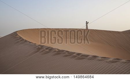 Man in traditional outfit praying in a desert at sunrise