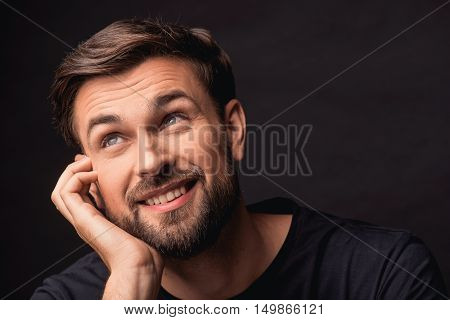 Happy young man is dreaming and smiling. He is leaning head on arm and looking up with aspiration. Isolated