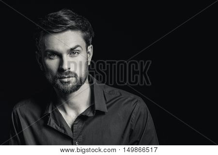 Sincere young man is looking at camera with inspiration. Isolated and copy space in right side. Black-and-white concept