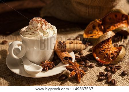Close-up of a cup of coffee with whipped cream cocoa powder cinnamon star anise and dried orange fruit