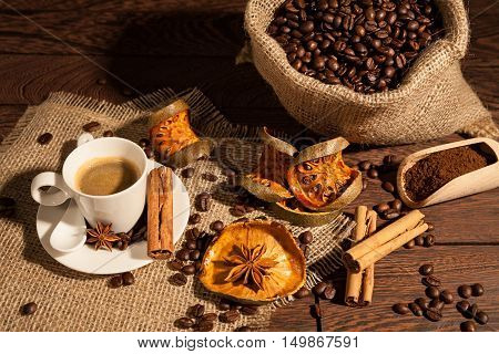 Coffee cup with cinnamon star anise dried orange fruit and coffee sack seen from above