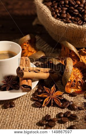 Close-up of coffee cup with cinnamon star anise dried orange fruit and a coffee sack on background