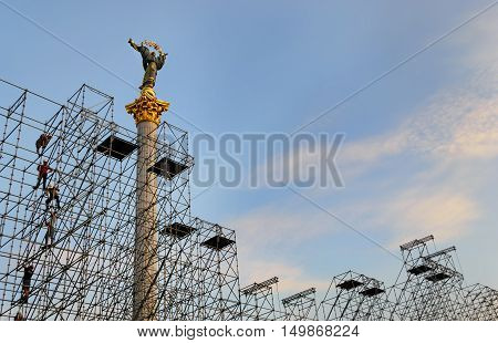 Independence Monument in Independence Square behind the scaffolding with workers in the construction site. Independence square Kiev Ukraine