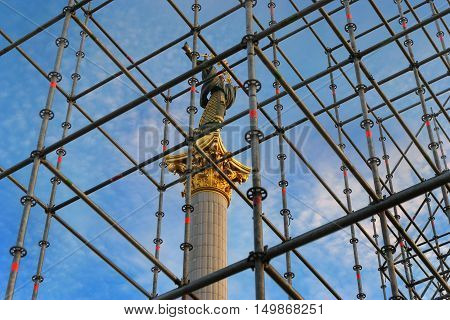 Independence Monument of Ukraine in Independence Square behind the scaffolding in the construction site. Kiev Ukraine