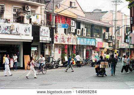 Shanghai, China - October 20, 2006: People go to the grocery store in a suburban street with typical houses and shops.
