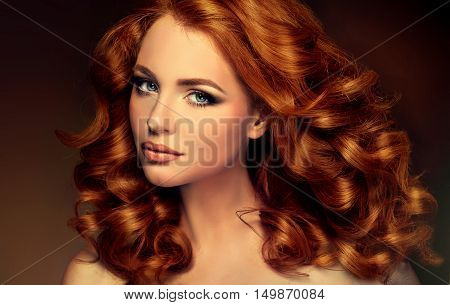 Girl with long and shiny wavy red hair . Beautiful model with curly hairstyle .