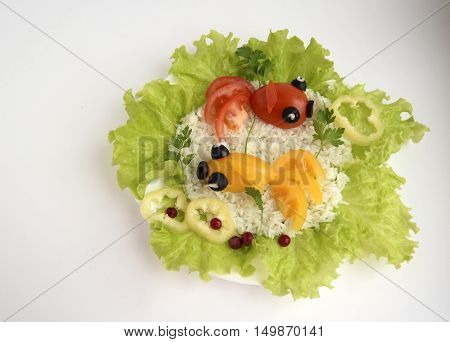 Fishes are made of tomatoes. Ridiculous food for good mood. The dish consists of tomatoes, olives, rice, salad, parsley.