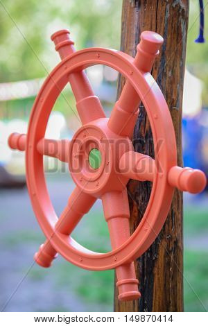 Red plastic children's handlebar of the ship a wooden girder on the playground