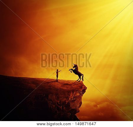 Idyllic view with a boy standing at the edge of a cliff chasm trying to tame a wild unicorn. Begining of a new friendship fearless symbol