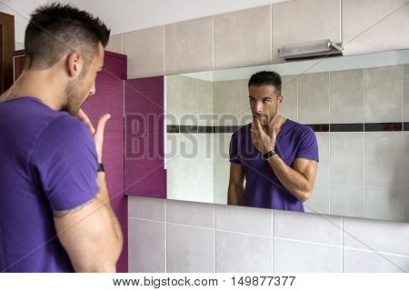 Handsome young man examining his stubble in bathroom mirror in the morning