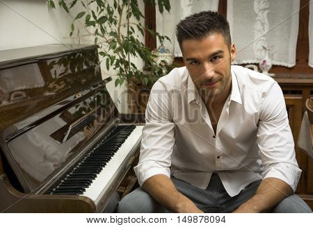 Young handsome male artist smiling while sitting next to his wooden classical upright piano, indoor portrait
