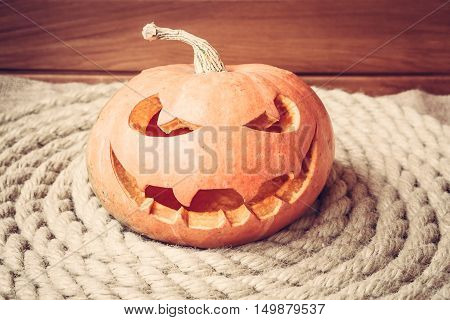 halloween pumpkin on coiled rope with wooden background