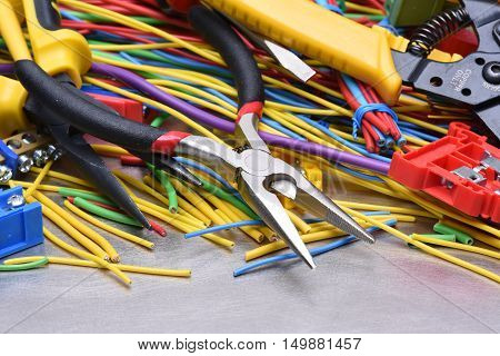 Electrical tools and cables used in electrical installations on grey metal background