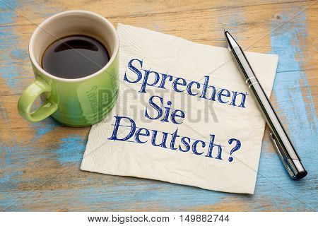 Sprechen Sie Deutsch? Do you speak German? Handwriting on a napkin with a cup of espresso coffee.