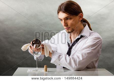 Wine Steward Fills Glass.
