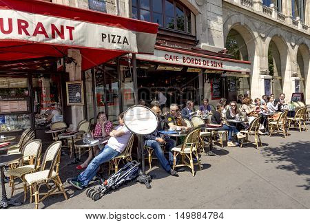 People Enjoy Sitting In The Sun In The Cafe