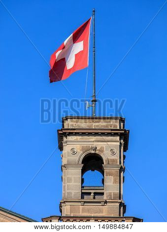 Flag of Switzerland on the Zurich main train station building in the city of Zurich Switzerland. Zurich main train station building (German: Zurich HB) was opened in 1871.