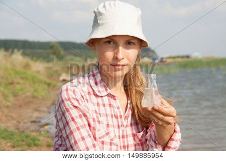 Water Purity Test. Woman holding chemical flask with water, lake or river in the background.