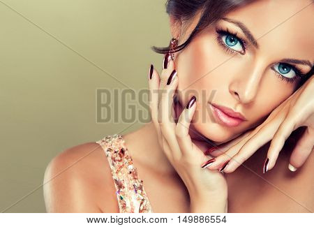 Beautiful model girl with pink metallic manicure on nails . Fashion makeup and cosmetics .