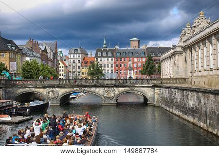 COPENHAGEN DENMARK - AUGUST 14 2016: View of canal boat with tourist and old bridge from bridge Prinsens Bro in Copenhagen Denmark on August 14 2016.