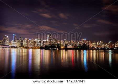 Deadman's Island, Stanley Park, Vancouver. The Vancouver skyline reflects in Burrard Inlet at night. British Columbia, Canada.