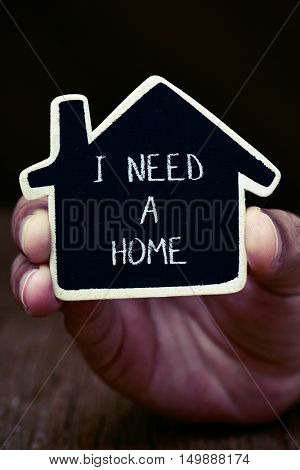 closeup of the hand of a young man showing a black house-shaped signboard with the text I need a home