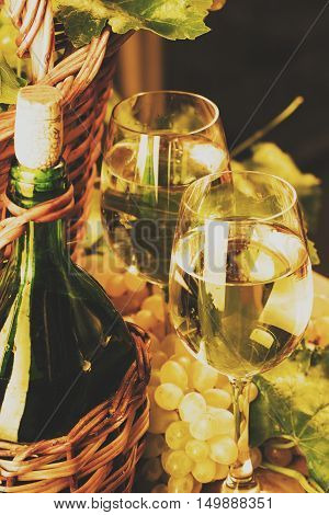 Two glasses of white wine, bottle of wite wine , white grapes with leaves in basket. Wine concept