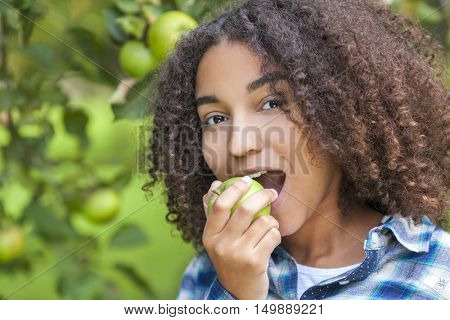 Outdoor portrait of beautiful happy mixed race African American girl teenager female child eating an organic green apple and smiling with perfect teeth