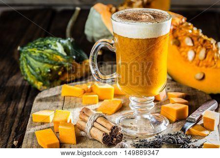 Pumpkin tea. Cup of autumm hot drink - pumpkin tea with milk cream and cinnamon and ingredients - fresh pumpkin, tea, cinnamon, nutmeg. Wooden rustic background