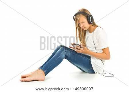 Young girl sitting on the floor with tablet pc smartphone and headphones over white background