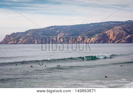Seascape at Guincho beach and Cascais coastline, Portugal, with a group of surfers in the water.