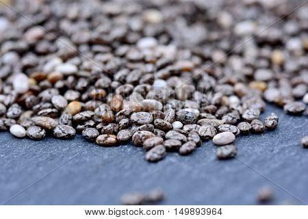 Many chia seeds on slate close up