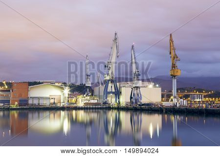 Monumental Cranes at sunrise in Shipyard. Night activity at the naval factories surrounding the city of Bilbao Spain.