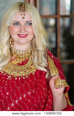 Smiling blonde woman in red dress and golden decorations.