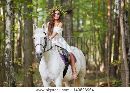 Barefooted girl in white dress with floral wreath on head sits on horseback in park.