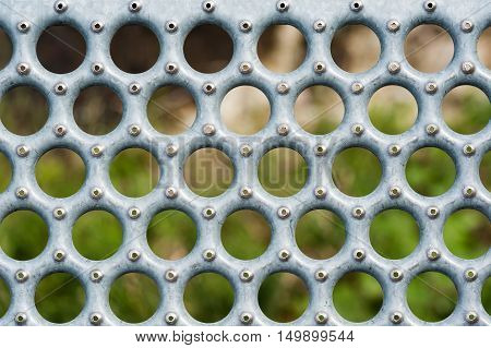 Detail of gray metal grate with round holes and rivets against blurred background.