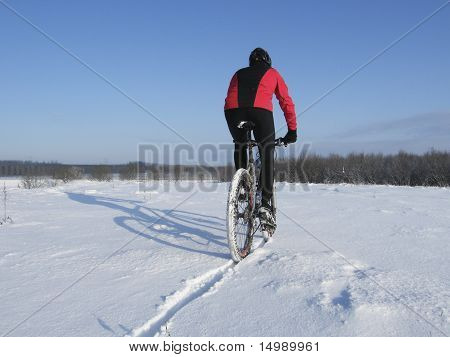 Mountainbiker Riding Snowy Trail