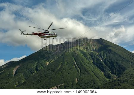 Kamchatka Peninsula, Russia - August 13, 2016: Tourist helicopter against the backdrop of volcano Priemysh. South Kamchatka Nature Park. View from the helicopter.