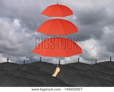 Red umbrella third layers in hand and rain protection more than black umbrellaconcept for management business idea on rain cloud background.