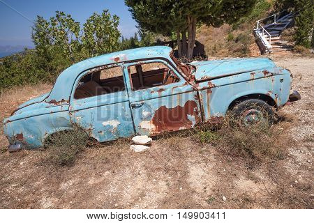 Rusted Car Stands In Summer Garden, Side View