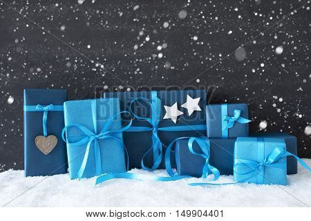 Blue Gifts Or Presents With Hearts And Stars. Black Cement Wall As Background With Snow And Snowflakes. Christmas Greeting Card For Seasons Greetings