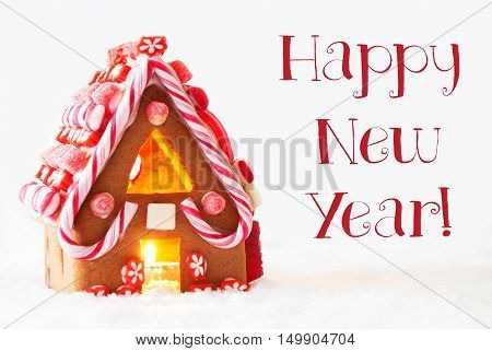 Gingerbread House In Snowy Scenery As Christmas Decoration With White Background. Candlelight For Romantic Atmosphere. English Text Happy New Year