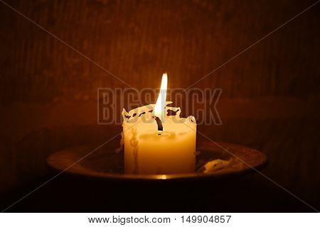 Big burning candle in a dim church