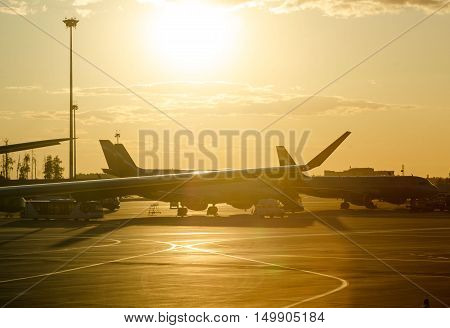 Evening airport in yellow dazzling sunset light.