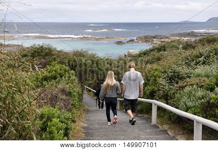 DENMARK,WA,AUSTRALIA-OCTOBER 2,2014: Tourists walking down path through coastal dunes to Green's Pool on the Great Southern Ocean coast in Denmark, Western Australia.