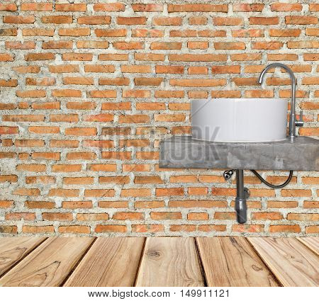 white basin and chrome faucet on brick wall and wooden floor