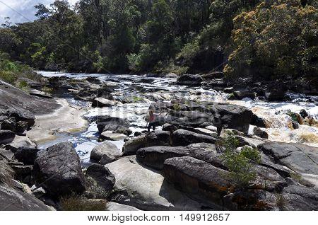 WALPOLE,WA,AUSTRALIA-OCTOBER 3,2014: Tourist climbing around the rocky Frankland River channel with circular pools in Walpole, Western Australia.
